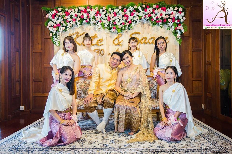 รีวิวชุดไทยเพื่อนเจ้าสาวแบบสไบสีขาวครีม ผ้าถุงสีชมพูอมม่วงสวยสุดๆ ในบรรายากาศเรือนไทยย่านรามคำแหงถ่ายภาพหมูกับบ่าวสาวพร้อมฉากหลังสวยงาม อีกแอคค่ะ